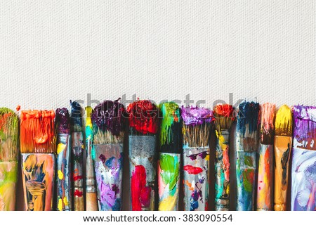 Row of artist paintbrushes closeup on artistic canvas. Royalty-Free Stock Photo #383090554