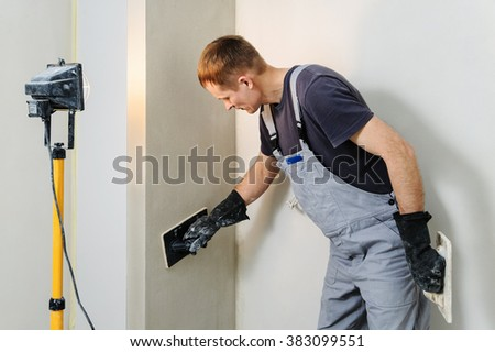 Worker makes final smoothing plaster on the wall using a plastic and Felt floats. #383099551
