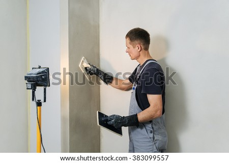 Worker makes final smoothing plaster on the wall using a plastic and Felt floats. #383099557