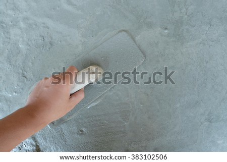 man hand plastering a wall with trowel, Selective focus. #383102506
