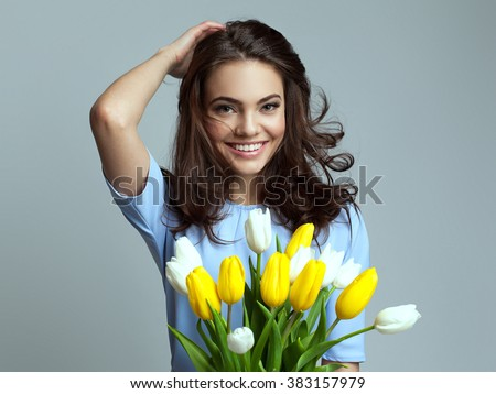 Beautiful girl in the blue dress with flowers tulips in hands on a light background #383157979