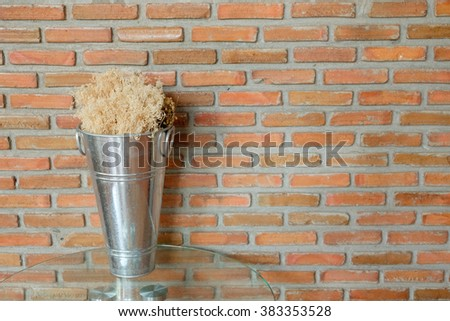 Dry tree in metal pot on top glass table in front of red brick wall. #383353528
