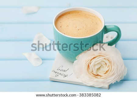 Coffee cup with spring flower and notes good morning on blue rustic background, breakfast on Mothers day or Womens day.