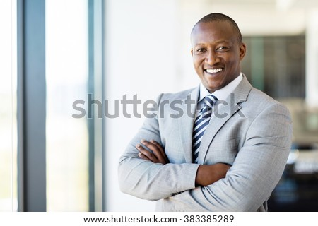 cheerful african american office worker with arms folded #383385289