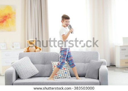 Little boy singing with a microphone on a sofa at home #383503000