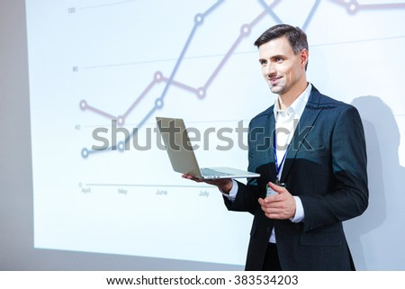 Happy speaker holding laptop and giving presentation in conference hall #383534203