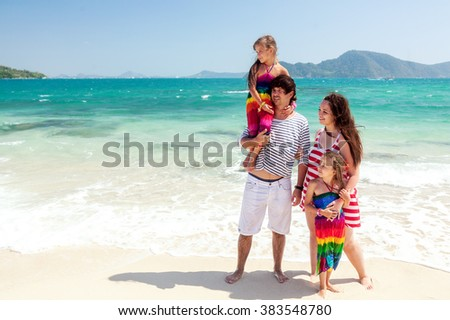 Mom, dad and two their kids walking at the tropical beach #383548780