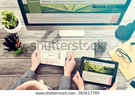 Designer's desk with responsive web ux design blueprint sketch concept. #383617789