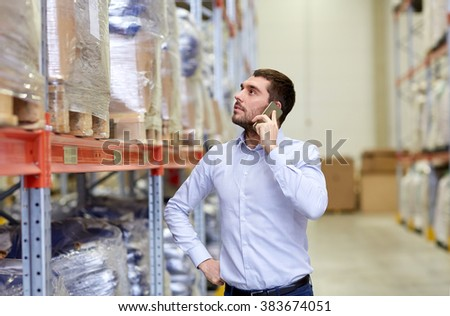 wholesale, logistic, business, export and people concept - serious businessman calling on smartphone at warehouse #383674051