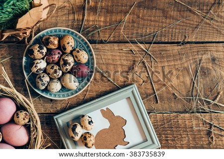 Easter table. Top view of Easter eggs on plates and Easter rabbit in picture frame lying on wooden rustic table with hay