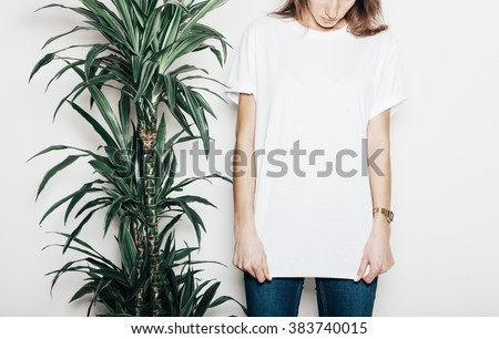 Young girl wearing blank t-shirt. Concrete wall background and green palm close the girl. Horizontal mockup #383740015