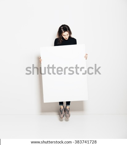 Photo of girl jumping in modern gallery and looking at the blank white canvas. Horizontal, mockup