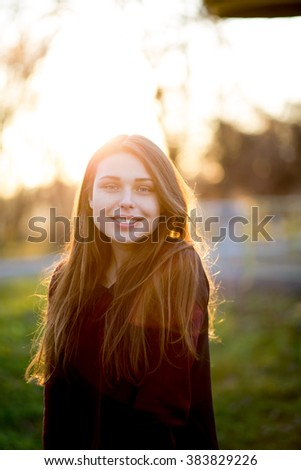 Portrait of beautiful young brunette girl in the Park #383829226