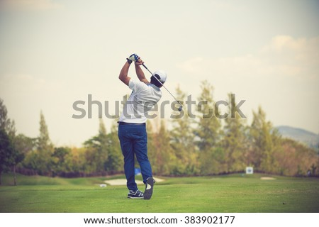 Golfers hit sweeping golf course in the summer vintage color #383902177