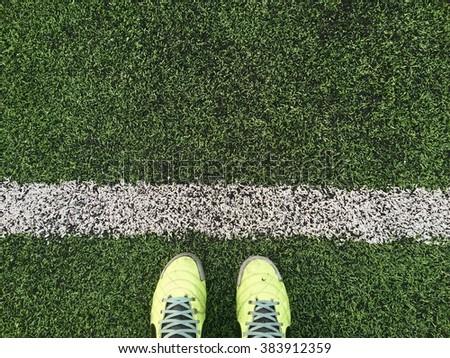 Green football boots. Green soccer boots on soccer field. #383912359