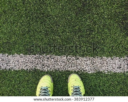 Green football boots. Green soccer boots on soccer field. #383912377