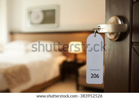 Opened door of hotel room with key in the lock Royalty-Free Stock Photo #383952526