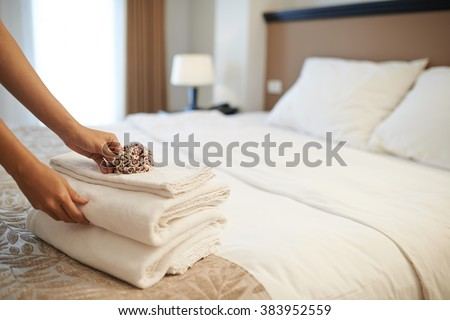 Hands of hotel maid putting flowers on the stack of towels #383952559
