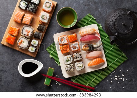 Set of sushi and maki roll and green tea on stone table. Top view #383984293