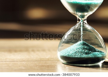 Sand running through the bulbs of an hourglass measuring the passing time in a countdown to a deadline, on a dark background with copy space. #384007933