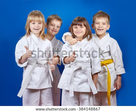 Four cheerful sportsman in karate gi are showing finger super #384148867