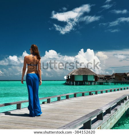 Woman on a tropical beach jetty at Maldives #384152620