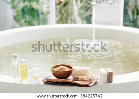 Spa decoration, natural organic products on a bathtube. Loofah, towel and frangipani flower Royalty-Free Stock Photo #384225742