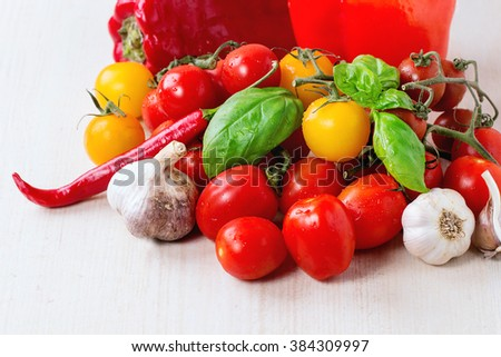 Assortment of colorful cherry tomatoes with pepper, garlic and basi over white wooden surface #384309997