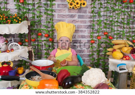 adorable baby cooking in kitchen. little cute child in costume of Cook. funny child makes a dinner. happy cute little baby in a cook cap laughs. Baby cook with vegetables in studio #384352822