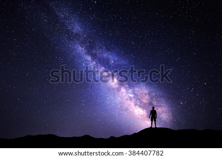 Landscape with Milky Way. Night sky with stars and silhouette of a standing happy man on the mountain. Royalty-Free Stock Photo #384407782