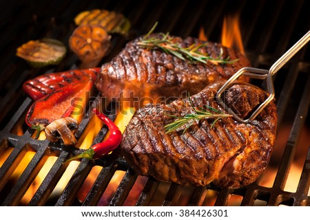 Beef steaks on the grill with flames #384426301