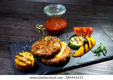 juicy two fried cutlets on a dish next to the peppers and tomatoes #384441613