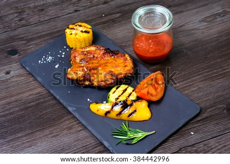 juicy grilled chicken with vegetables on a basalt slab #384442996