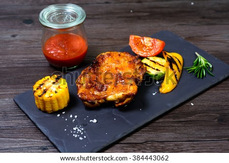 juicy grilled chicken with vegetables on a basalt slab #384443062