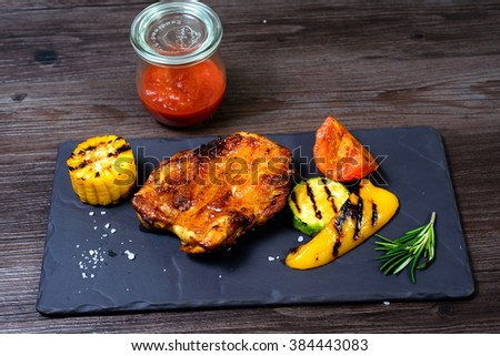 juicy grilled chicken with vegetables on a basalt slab #384443083