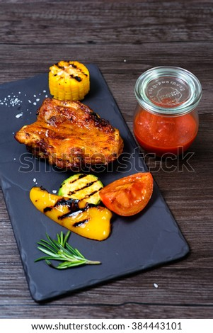 juicy grilled chicken with vegetables on a basalt slab #384443101