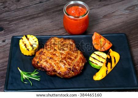 juicy roasted pork with vegetables on a basalt slab #384465160