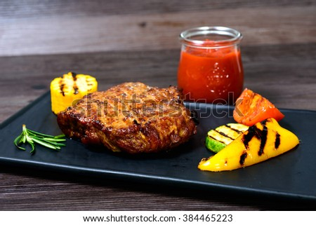 juicy roasted pork with vegetables on a basalt slab #384465223