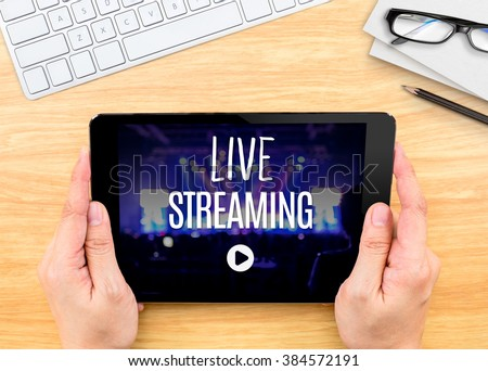 Hand holding tablet with Live Streaming word on wood table ,Internet marketing concept. #384572191