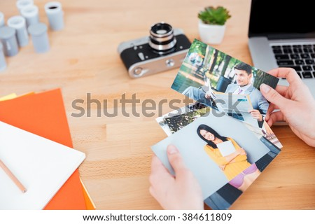 Top view of photos of models holded by young woman photographer at the table
