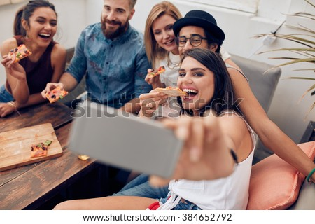 Group of multiracial young people taking a selfie while eating pizza. Young woman eating pizza her friends sitting around during a party. Royalty-Free Stock Photo #384652792