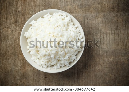 Jasmine rice isolated on wooden table #384697642