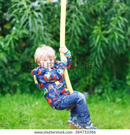 Little smiling boy of three years having fun on swing on sunny summer day, outdoors. Active sports with kids. #384710386