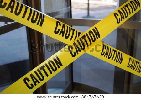 Yellow CAUTION tape barring exit through a door Royalty-Free Stock Photo #384767620