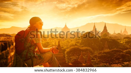 Young traveller enjoying a looking at sunset on Bagan, Myanmar Asia. Panoramic view. Traveling along Asia, active lifestyle concept.  Royalty-Free Stock Photo #384832966