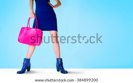 Beautiful legs woman with blue boots and pink bag. Isolated on blue with copy space. Fashion shopping image.  #384899200