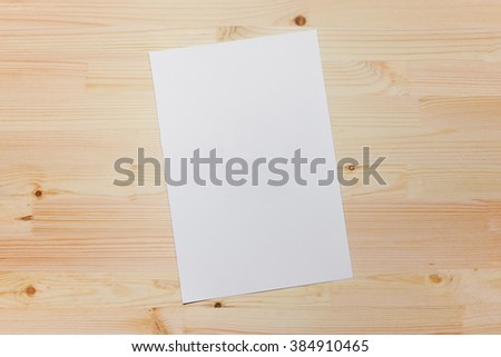 Mock up, photo paper on the table, art tools, white sheet, a wooden table. Background light wood #384910465