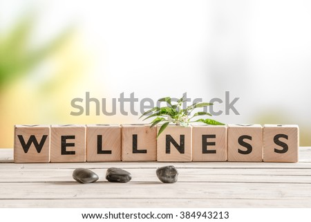 Wellness sign with wooden cubes and flowers and stones Royalty-Free Stock Photo #384943213