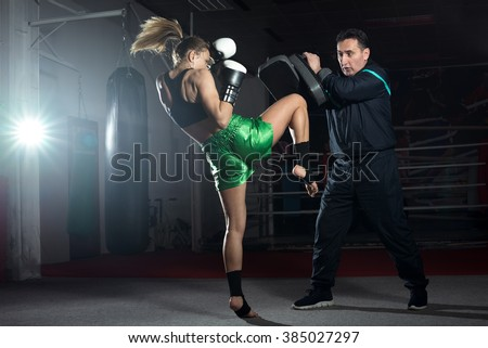 Girl doing knee kick exercise during kickboxing training with personal trainer Royalty-Free Stock Photo #385027297