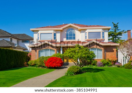 Big custom made luxury house with nicely trimmed and landscaped front yard in the suburbs of Vancouver, Canada. #385104991